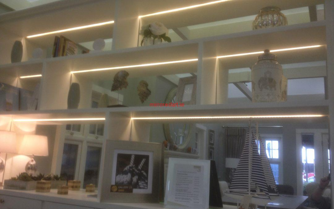 Mirrors set into bookshelves with led lighting, giving incredible depth to the room.